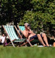 En man solar i en park i London. Alberto Pezzali / TT NYHETSBYRÅN