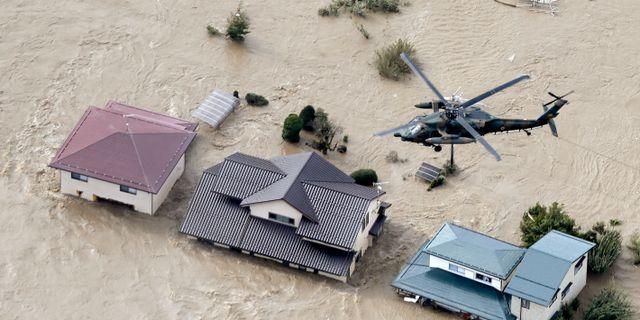 En räddningshelikopter arbetar över ett översvämmat område. KYODO / TT NYHETSBYRÅN