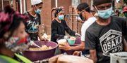 Människor i Sydafrika hämtar ut matlådor under pandemin. MARCO LONGARI / TT NYHETSBYRÅN