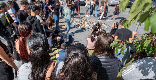 Sörjande människor vid den plats i Botkyrka där en 12-årig flicka sköts ihjäl. Stina Stjernkvist/TT / TT NYHETSBYRÅN