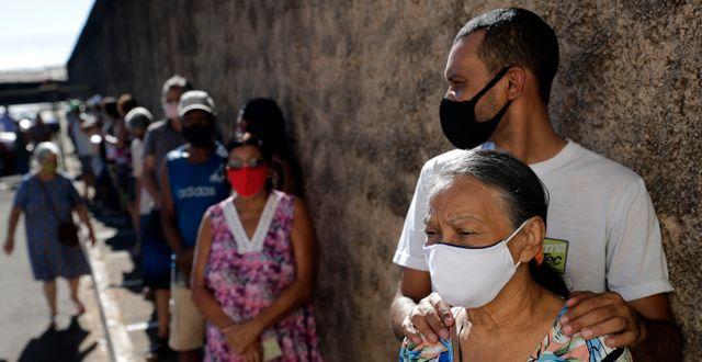 Människor i Brasilien väntar på att få vaccin. Eraldo Peres / TT NYHETSBYRÅN