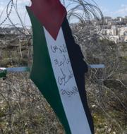 Palestinsk flagga framför bosättning.  TT