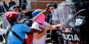 En kvinna grips av polis i Manugua. INTI OCON / AFP
