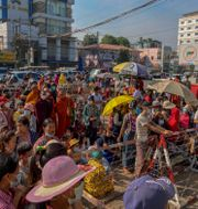 Människor har samlats utanför ett fängelse i Rangoon för att se fångar släppas.  STR / TT NYHETSBYRÅN