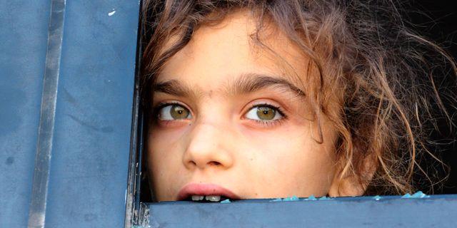 En flicka som evakuerats från en av de två regimtrogna byarna. IBRAHIM YASOUF / AFP