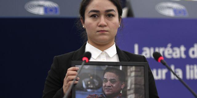 Jewher Ilham håller upp ett foto på sin fängslade far Ilham Tohti.  FREDERICK FLORIN / AFP