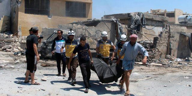 Räddningsarbetare och civila bär en kropp efter luftanfall mot staden Hish i Idlibprovinsen i Syrien. TT NYHETSBYRÅN/ NTB Scanpix