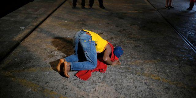 Illustrationsbild: Person som kysser marken efter landstigning i Malaga. JON NAZCA / TT NYHETSBYRÅN