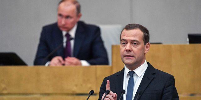 Arkivbild: Premiärminister Dimitrij Medvedev med president Vladimir Putin i bakgrunden.  YURI KADOBNOV / AFP