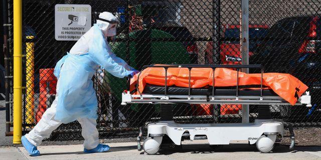 Sjukvårdspersonal för bort en avliden person i New York. ANGELA WEISS / TT NYHETSBYRÅN