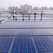 Workers walk on a roof of the Theme Pavilion for the 2010 World Expo covered by solar panels in Shanghai, China. TT NYHETSBYRÅN
