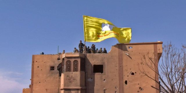 Kurdiska styrkor hissar sin flagga på toppen av en byggnad i staden Baghuz, som har beskrivits som IS sista fäste i Syrien.  HANDOUT / RONAHI TV