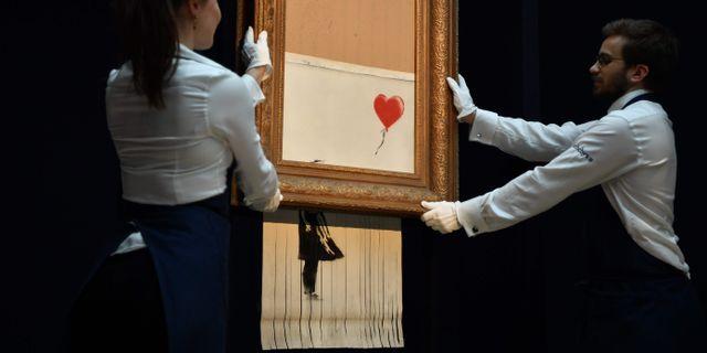 """Sotheby's-anställda håller upp Banksy-verket """"Flicka med ballong"""", som till hälften strimlades efter auktionen förra veckan.  BEN STANSALL / AFP"""