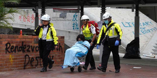 En demonstrant eskorteras ut från campuset av sjukvårdspersonal.  Vincent Yu / TT NYHETSBYRÅN