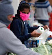 En kvinna handlar i London under pandemin. Frank Augstein / TT NYHETSBYRÅN