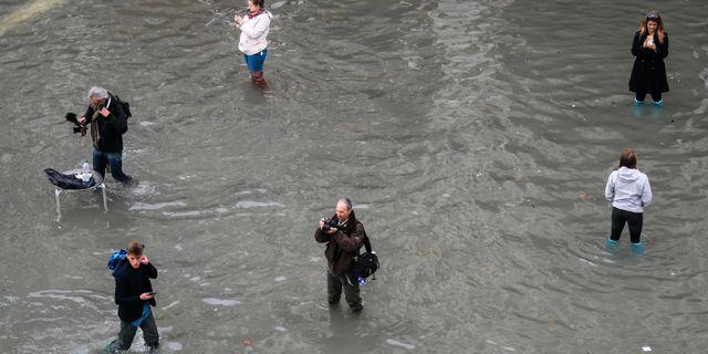 Människor fotograferar förödelsen.  MARCO BERTORELLO / AFP