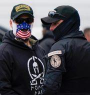 Personer utanför Kapitolium med Oath Keepers emblem på sina kläder.  Jacquelyn Martin / TT NYHETSBYRÅN