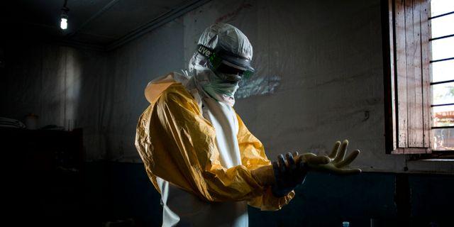 En hjälparbetare sätter på sig skyddskläder.  JOHN WESSELS / AFP