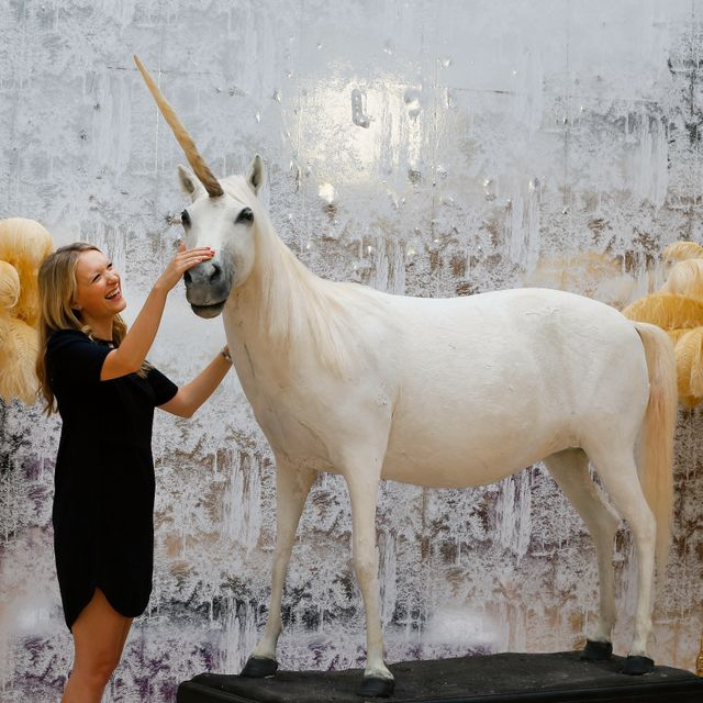 """Kate Summers, Christie's Head of Sale for the auction strokes a model of a unicorn, Equus Caballus, during a press preview at Christie's auction rooms in London, Monday, Aug. 3, 2015. The unicorn estimated at 4,000-6,000 pounds ($6,000-$9,000 US dollars) will be auctioned in the """"Out of the Ordinary"""" sale on Sept. 10 in London. Kirsty Wigglesworth / TT NYHETSBYRÅN"""