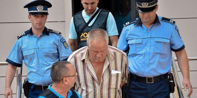 Gheorghe Dinca förs bort från domstolen i Craiova i södra Rumänen. Bogdan Danescu / TT NYHETSBYRÅN
