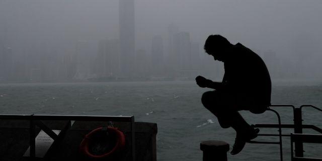 En man sitter i Victoria Harbour i Hong Kong i väntan på stormen Vincent Yu / TT NYHETSBYRÅN