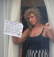 """En kvinna protesterar mot krav på karantän på hotell. """"Jag har ett hem att isolera mig i"""", skriver hon på en skylt. Jonathan Brady / TT NYHETSBYRÅN"""
