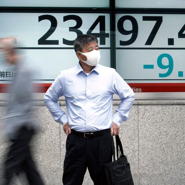 A man stands near an electronic stock board showing Japan's Nikkei 225 index at a securities firm in Tokyo Friday, Oct. 16, 2020. Eugene Hoshiko / TT NYHETSBYRÅN