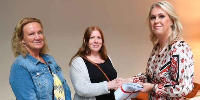 Undersköterskorna Jenny Klingstam och Mari Viberg lämnar över namninsamlingen till Lena Hallengren.  Fredrik Sandberg/TT / TT NYHETSBYRÅN