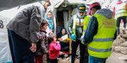 Masker delas ut i flyktinglägret i Moria på Lesbos i Grekland. MANOLIS LAGOUTARIS / TT NYHETSBYRÅN