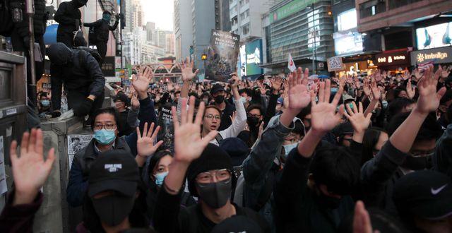 Demonstranter i Hongkong håller upp handen som en symbol för de fem krav som de vill ska bli mötta.  Kin Cheung / TT NYHETSBYRÅN
