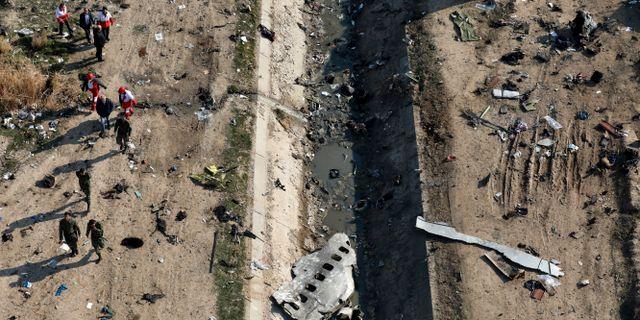 Räddningsarbetare söker igenom platsen efter flygkraschen. Ebrahim Noroozi / TT NYHETSBYRÅN