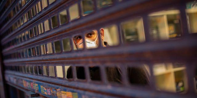 En man med ansiktsmask bakom ett galler i centrala Madrid. Bernat Armangue / TT NYHETSBYRÅN