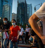 Människor med ansiktsmask i Peking. Illustrationsbild. Mark Schiefelbein / TT NYHETSBYRÅN