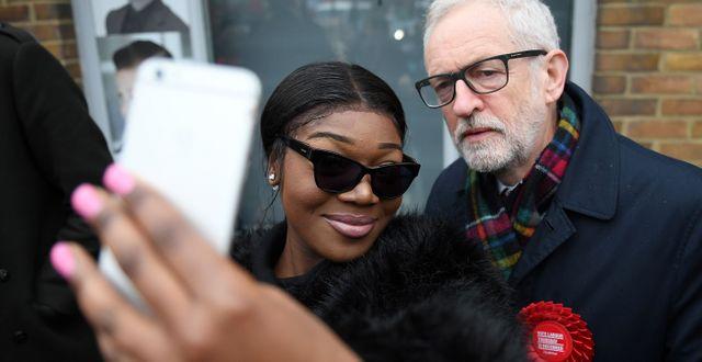 En kvinna tar en selfie tillsammans med oppositionspartiet Labours ledare Jeremy Corbyn utanför en vallokal i London.  DANIEL LEAL-OLIVAS / AFP