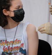 En kvinna i Rumänien får Pfizers vaccin.  Andreea Alexandru / TT NYHETSBYRÅN