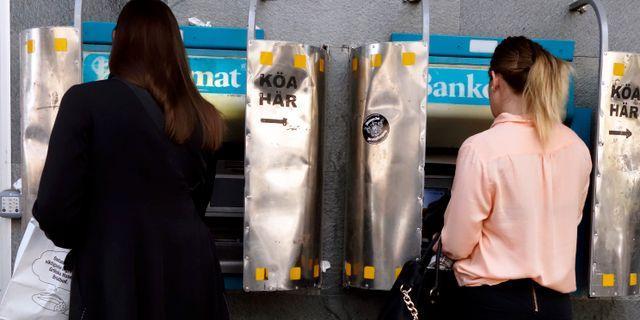 Arkivbild. Två kvinnor tar ut pengar från varsin bankomat.  Hasse Holmberg / TT / TT NYHETSBYRÅN