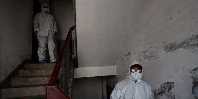 Sjukvårdsarbetare knackar dörr i Wuhan. CHINA DAILY / TT NYHETSBYRÅN