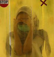 Kvinna spolas med desinfektion. Dita Alangkara / TT NYHETSBYRÅN
