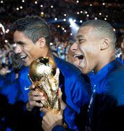 Frankrikes Kylian Mbappe och Raphael Varane efter deras VM-finalsegern över Kroatien 2018. CHARLES PLATIAU / BILDBYRÅN