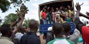 Tidigare fångar vinkar vinkar efter att ha släppts från ett fängelse i huvudstaden Bujumbura. STRINGER / AFP