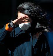 Kinesisk kvinna med munskydd kommer gåendes på en gata.  Andy Wong / TT NYHETSBYRÅN