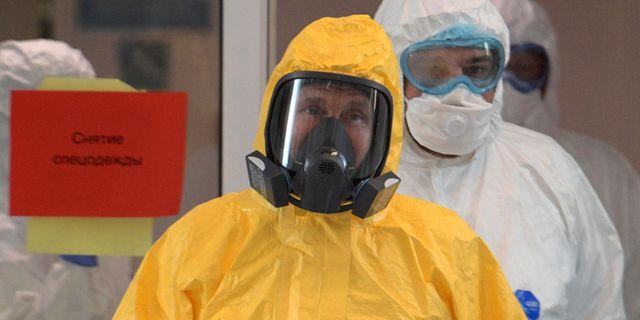 Vladimir Putin i skyddsdräkt under ett sjukhusbesök. ALEXEY DRUZHININ / TT NYHETSBYRÅN