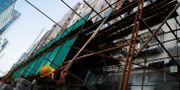 Illustrationsbild: Två män bygger en byggställning i centrala Peking.  Thomas Peter / TT NYHETSBYRÅN