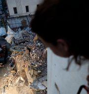 En person på en balkong överblickar räddningsarbetet. Hussein Malla / TT NYHETSBYRÅN