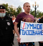 """Rysk polis griper en oppositionell man som bär ett plakat med texten """"smart röstning"""".  Alexander Zemlianichenko / TT NYHETSBYRÅN"""