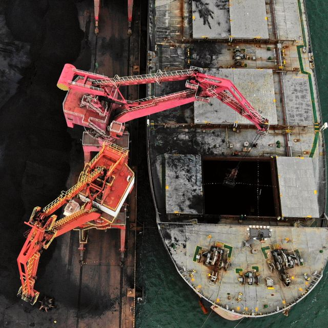 In this photo released by Xinhua News Agency, machines load imported coal from a cargo vessel docked at a port in Rizhao in east China's Shandong province on Nov. 21, 2019. Wang Kai / TT NYHETSBYRÅN