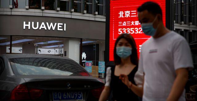 Två personer utanför en Huawei-butik i Kina.  Mark Schiefelbein / TT NYHETSBYRÅN