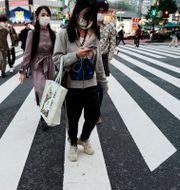 Illustrationsbild: Människor med munskydd vid ett övergångsställe i Tokyo.  Eugene Hoshiko / TT NYHETSBYRÅN