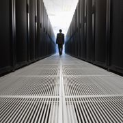 Rear view of businessman walking in server room in Cape Town, South Africa Shutterstock
