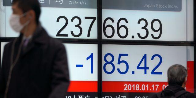 Människor går förbi en informationstavla utanför ett finansbolag i Tokyo på onsdagen. Eugene Hoshiko / TT NYHETSBYRÅN